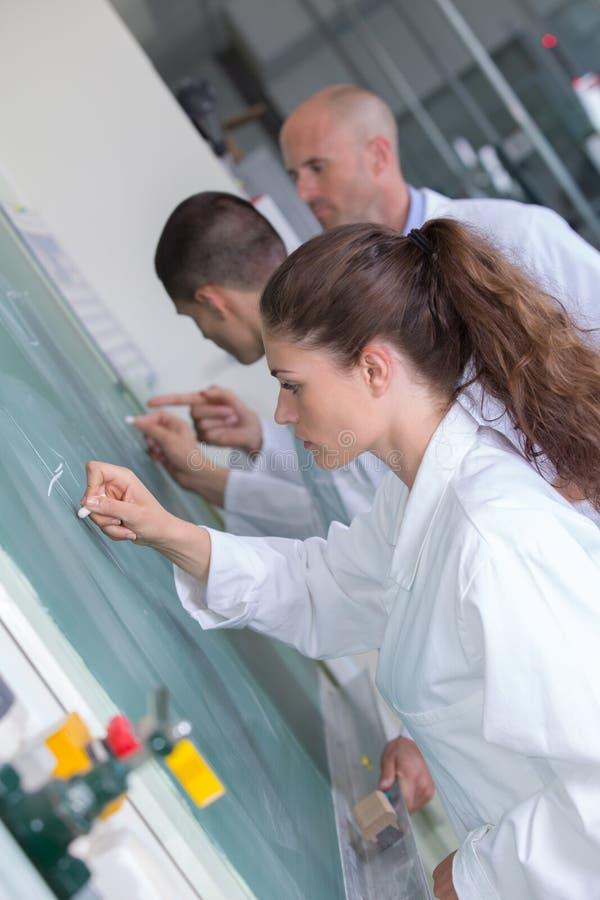 Młodzi ucznie pisze liczbach na zielonej kredowej desce w sala lekcyjnej zdjęcie royalty free