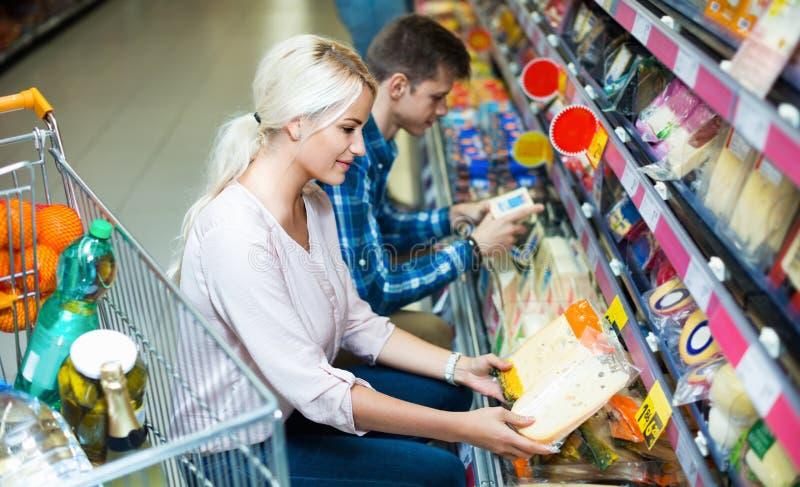 Młodzi współmałżonkowie kupuje cheddara w serowej sekci obraz royalty free
