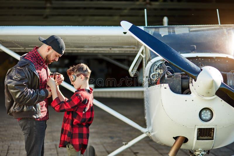 Młodzieżowi i młodzi męscy aeromodellers stoją blisko jednosilnikowego samolotu zdjęcia stock