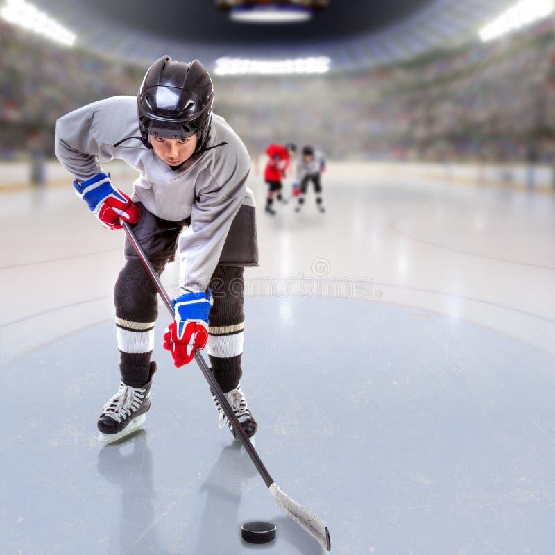 Młodzieżowy gracz w hokeja krążek hokojowy Obchodzi się w arenie obrazy royalty free