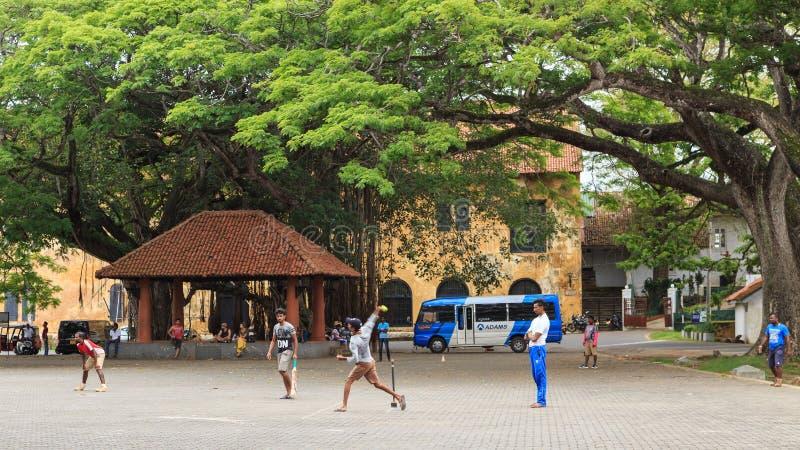 Młodzienowie bawić się krykieta w wioska kwadracie - fortu Galle Sri lanka zdjęcia stock