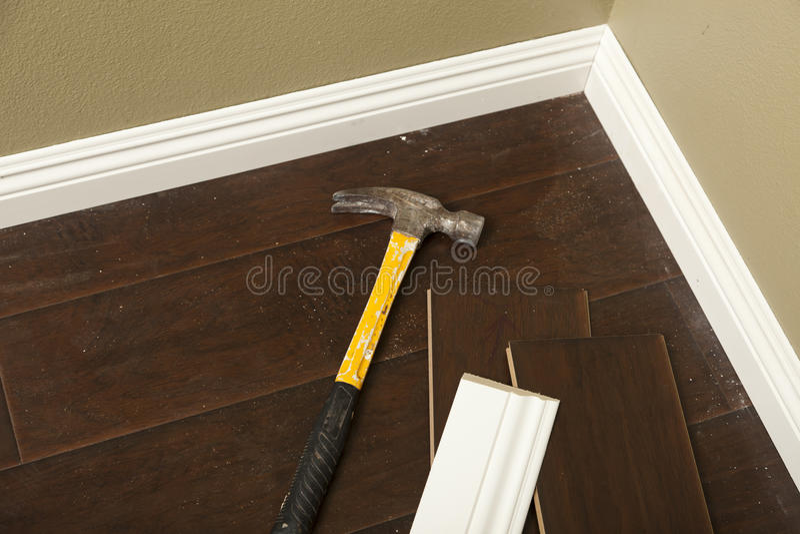 Młot, laminat podłoga i Nowy Baseboard formierstwo, zdjęcia stock