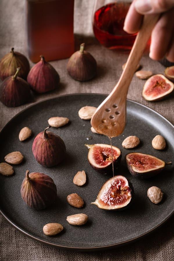 Mżysty miód na talerzu figi i migdały obraz stock