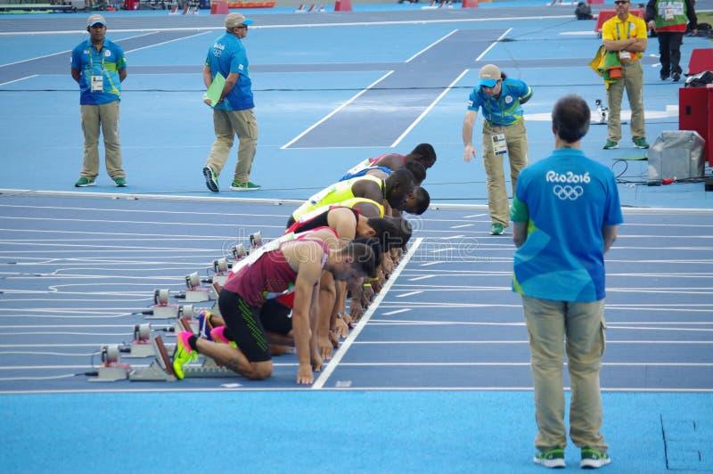 100m短跑奔跑起动线的运动员  免版税库存图片