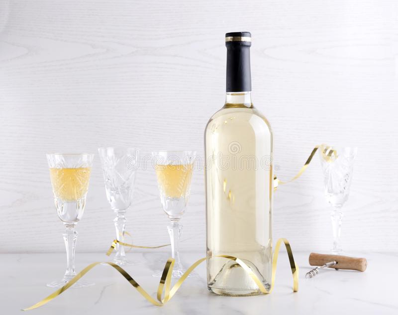 m Μπουκάλι του άσπρων κρασιού και των γυαλιών κρασιού, ντεκόρ διακοπών στον άσπρο πίνακα στο ελαφρύ κλίμα στοκ εικόνα