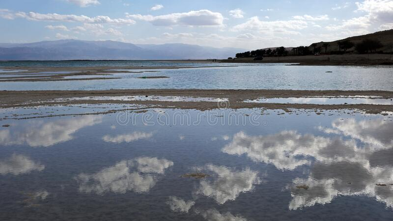 Sky reflections on drying waters of Dead sea, Israel. At -430 m below sea level it is the lowest surface on the Earth-waters of Dead sea are receding at an royalty free stock photography