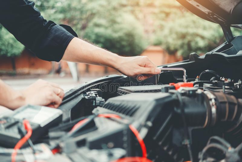 M?canicien automobile travaillant dans le technicien Hands de garage du m?canicien de voiture travaillant batterie de voiture dan images libres de droits