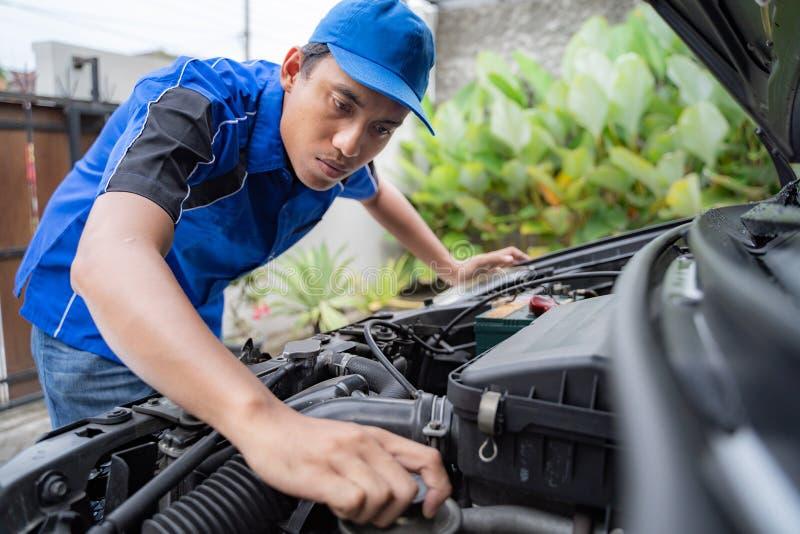 M?canicien faisant une certaine inspection sur le moteur de voiture image libre de droits