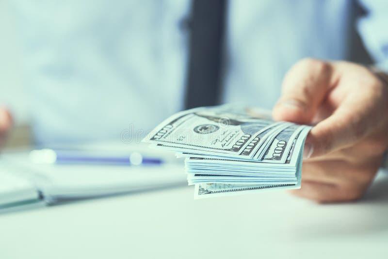 M??czyzna daje pieni?dze dolara ameryka?skiego banknotom i trzyma spieni??a wewn?trz r?ki Pieni?dze kredytowy poj?cie Stonowany o zdjęcie stock