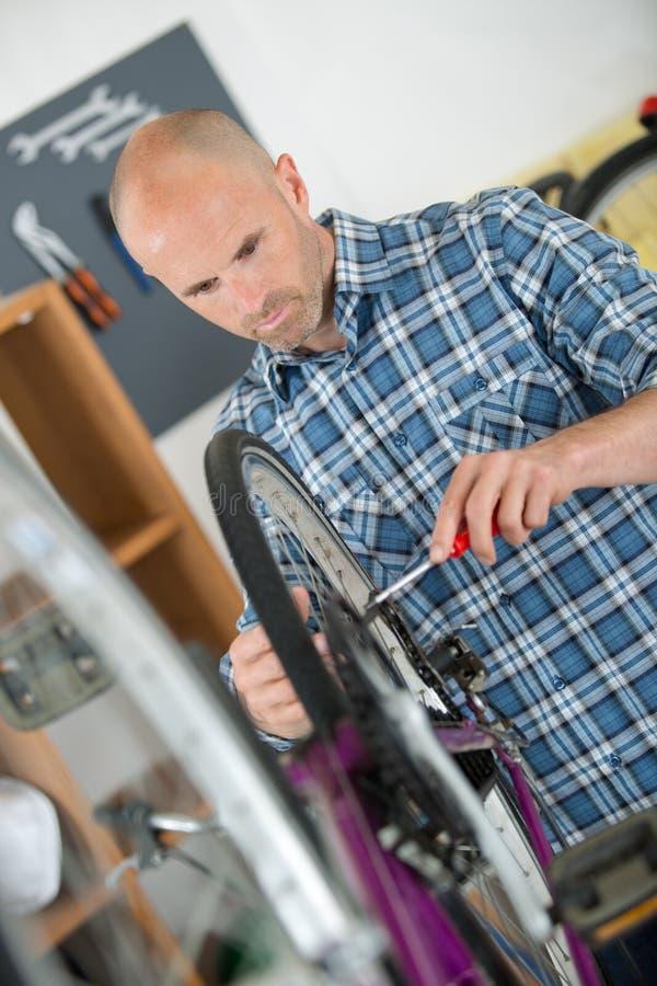 M??czyzna mechanika naprawiania rowerowi bicykle obrazy royalty free