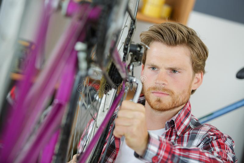 M??czyzna mechanika naprawiania rowerowi bicykle zdjęcie royalty free