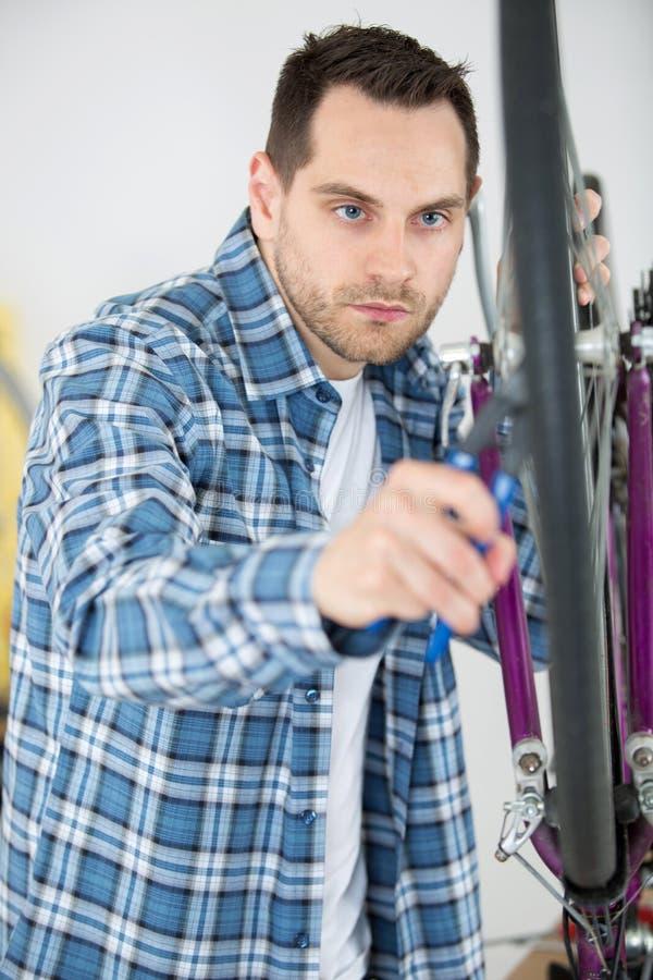 M??czyzna naprawiania rower toczy wewn?trz sklep zdjęcie stock