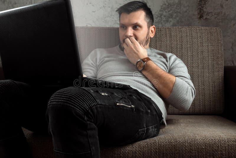 M??czyzna ogl?da doros?ego wideo na laptopie podczas gdy siedz?cy na le?ance Poj?cie porn, m??czyzna potrzeby, deprawuje, ??dza,  obrazy stock
