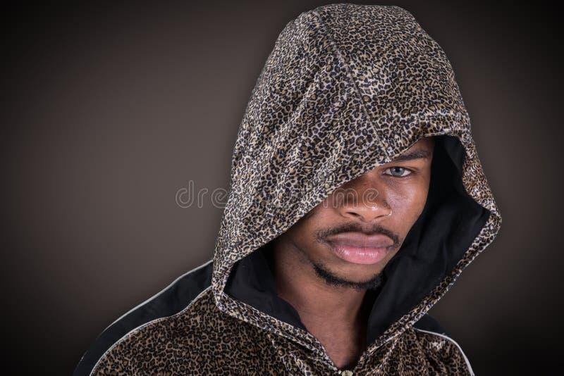 M??czyzna patrzeje kamer? na czarnym tle w hoodie fotografia royalty free