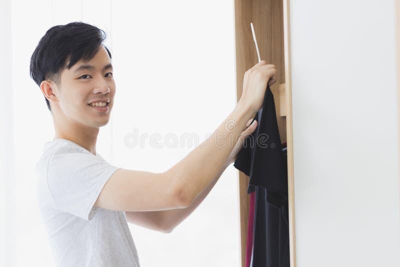 M??czyzna podnosi w g?r? czarnej koszulki od garderoby zdjęcie royalty free