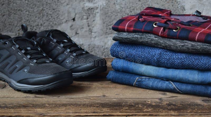 M??czyzna przypadkowy str?j Men& x27; s buty, odzie? i akcesoria na drewnianym tle, - pulower, cajgi, sneakers Odg?rny widok Mies fotografia royalty free
