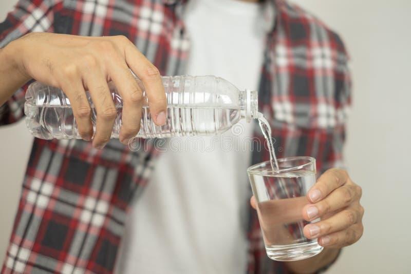 M??czyzna r?ka trzyma butelk? wodna dolewanie woda w szk?o zdjęcie stock