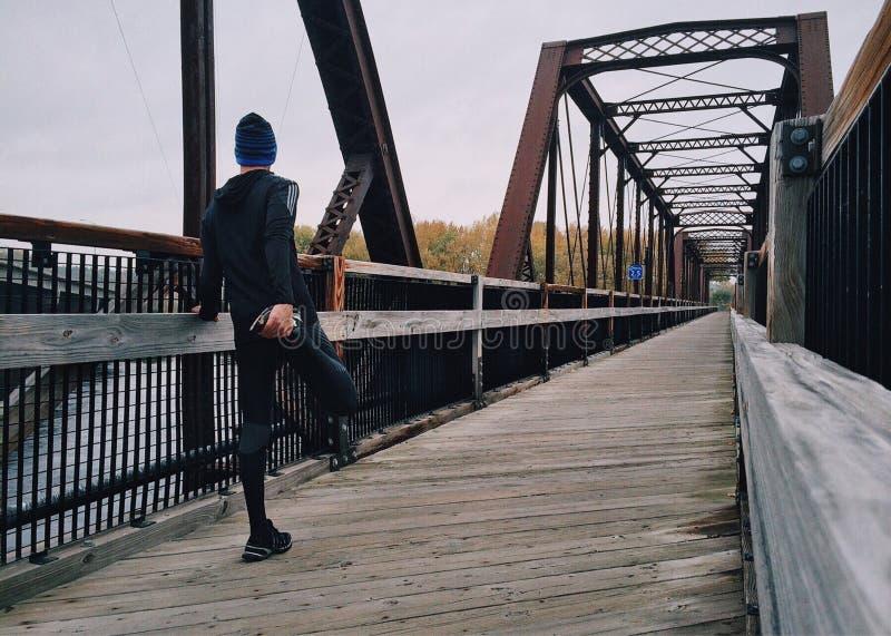 Mężczyzna rozciągania noga na footbridge obraz royalty free