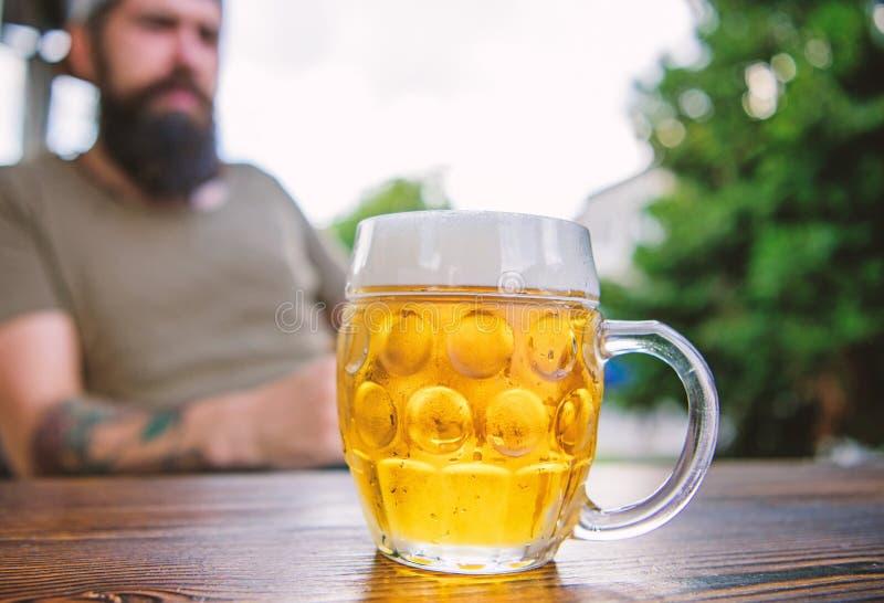 M??czyzna siedzi kawiarni tarasowy cieszy si? piwny defocused Alkoholu i baru poj?cie Kreatywnie m?ody piwowar Rzemios?a piwo jes obrazy stock