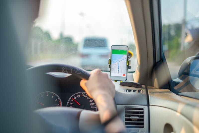 M??czyzna siedzi w samochodowej r?ce jedzie samoch?d na drodze otwiera GPS zastosowanie podróż jest przyglądający drogowego ruchu fotografia stock