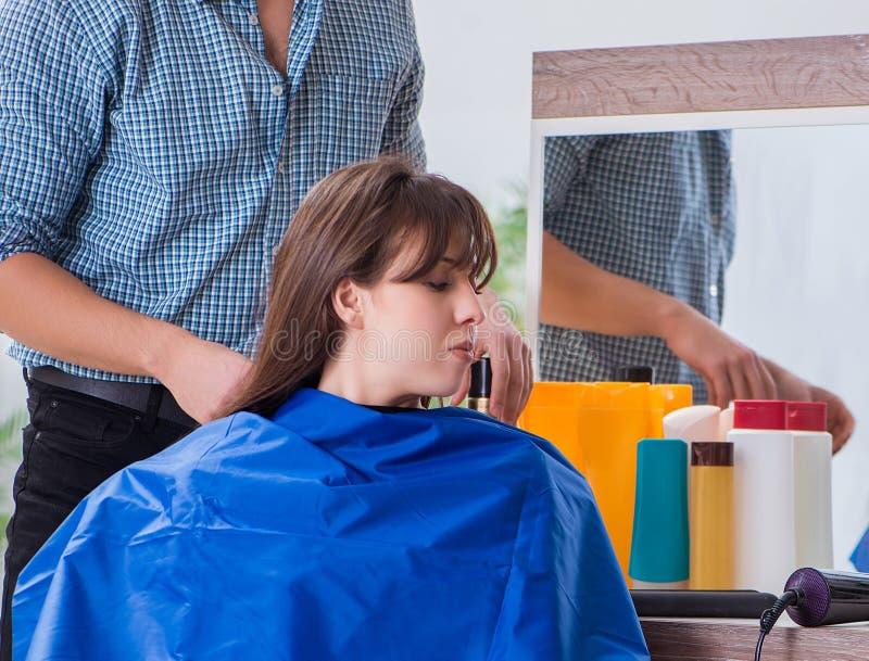 M??czyzna m?ski fryzjer robi ostrzy?eniu dla kobiety obraz royalty free