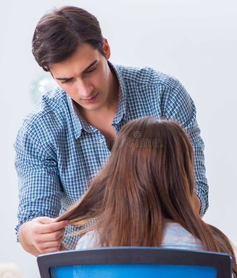 M??czyzna m?ski fryzjer robi ostrzy?eniu dla kobiety zdjęcie stock