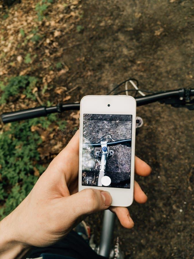M??czyzna trzyma jego smartphone chwyta jego rowerowy na wiosna lasowym ?ladzie rower zdjęcia stock