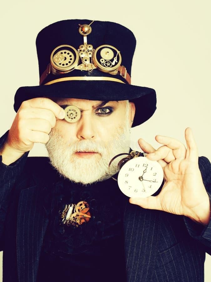 M??czyzna utrzymuje cogwheel i zegar obraz royalty free