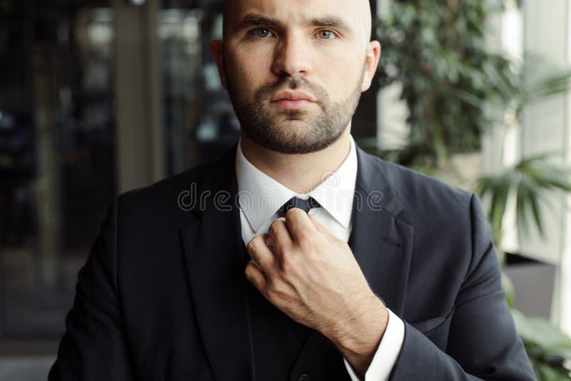 M??czyzna w czarnym kostiumu prostuje jego krawat obraz stock