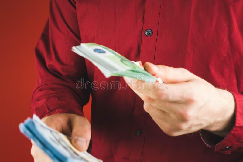 m??czyzna w czerwonych koszulowych mienie plikach pieni?dze na czerwonym tle obraz royalty free
