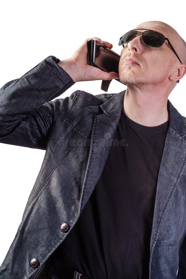 M??czyzna w drelichowej kurtce, b?d?cy ubranym okulary przeciws?oneczni, opowiada na telefonie kom?rkowym zdjęcie stock