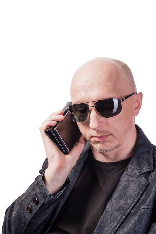 M??czyzna w drelichowych kurtki i by? ubranym okularach przeciws?onecznych, opowiada na telefonie kom?rkowym obraz royalty free