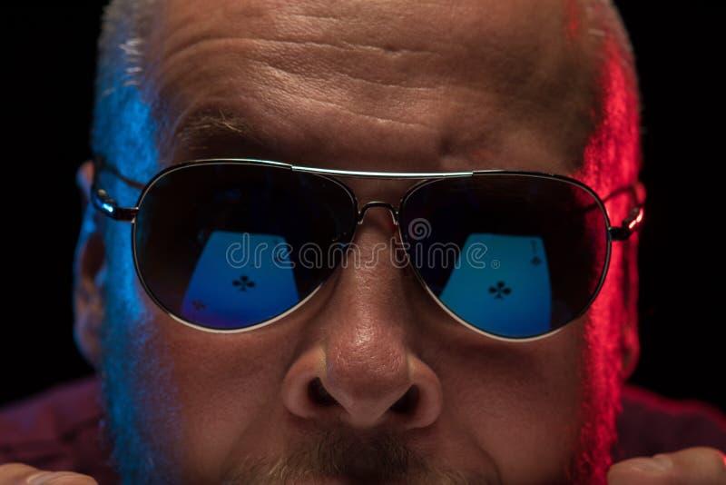 M??czyzna w okularach przeciws?onecznych trzyma pok?ad karty do gry i przedstawienie sztuczki obraz stock