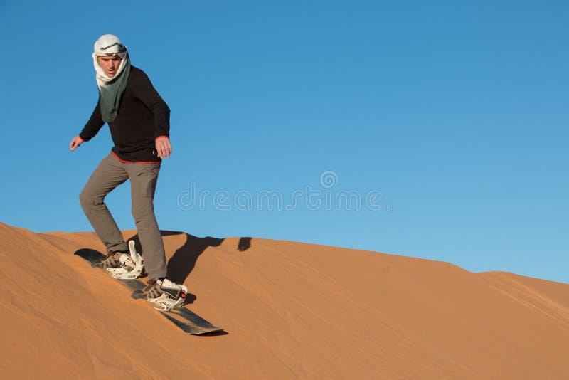 M??czyzna z chustki na g?ow? ?wiczy sandboarding w pustynnych diunach erg Chebbi zdjęcie stock