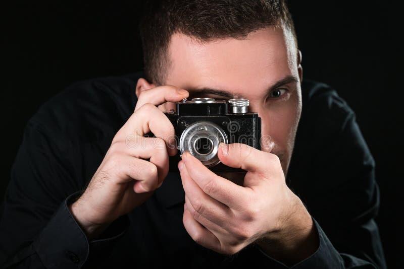 M??czyzny fotograf trzyma retro fotografii kamer? Mkn?cy proces Fotograf?w spojrzenia przy viewfinder zdjęcie royalty free
