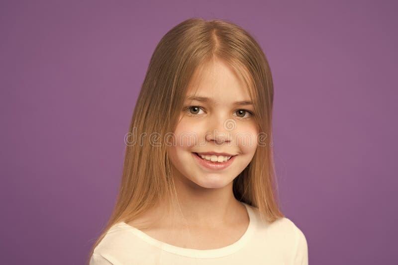M?dchen auf l?chelndem Gesicht mit dem langen Haar tr?gt wei?es Hemd, violetten Hintergrund M?dchen mag nett, stilvoll schauen un lizenzfreie stockbilder