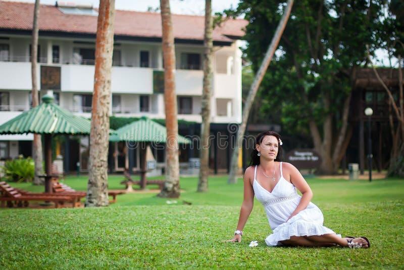 M?dchen, das auf dem Rasen stillsteht Braut auf Flitterwochen Hotelgebiet Entspannungsbereich Frau, die auf einem gr?nen Rasen si stockbild