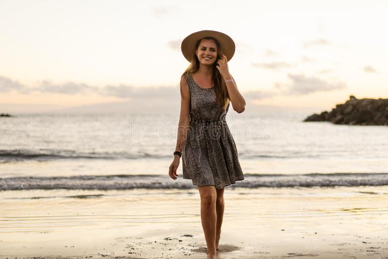 M?dchen, das auf den Strand bei Sonnenuntergang geht stockfotografie