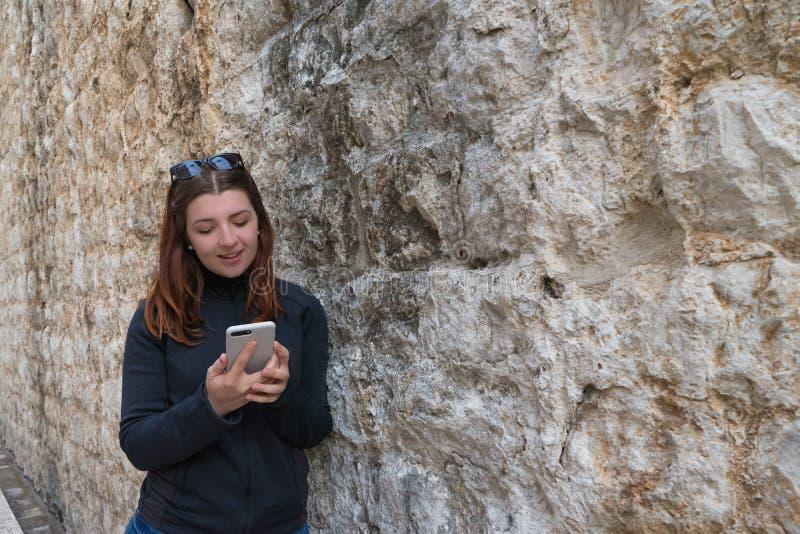 M?dchen, das auf Steinbacksteinmauer der alten mittelalterlichen Stra?e baut Rothaarige Schreibensmartphone junge Frau unter Verw lizenzfreie stockfotografie