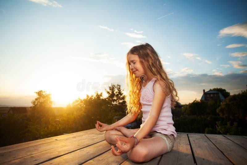 M?dchen, das bei Sonnenuntergang meditiert stockbild