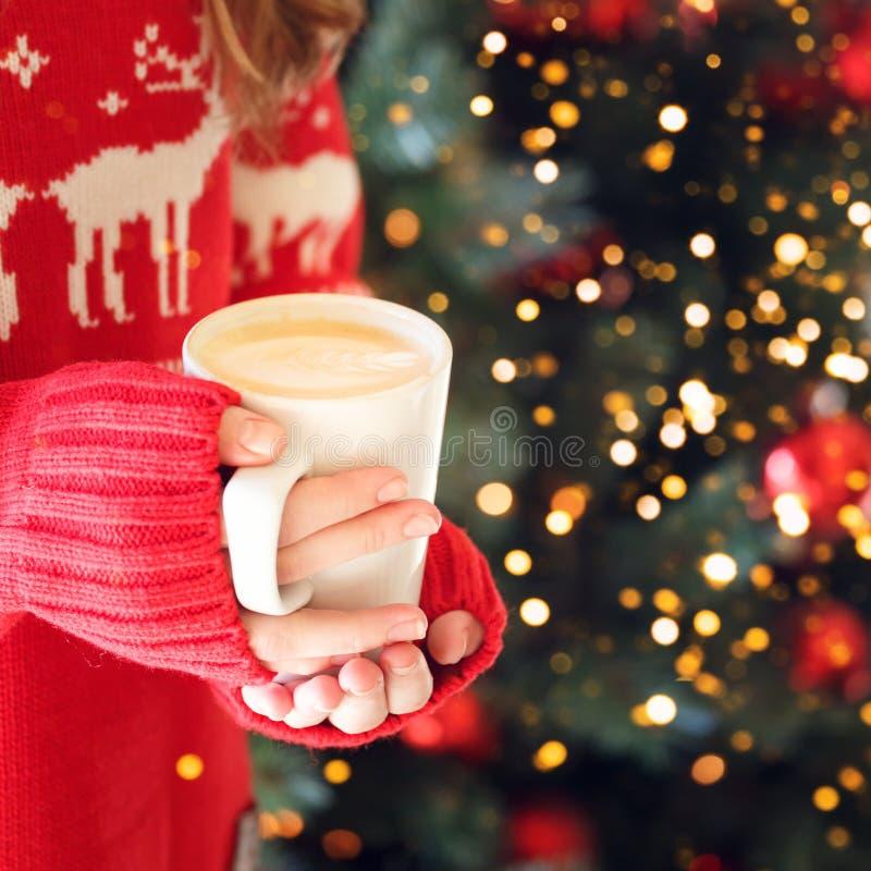 M?dchen, das eine Cappuccinoschale h?lt Konzept des Weihnachtsfeiertags Gelbe und rote Farben Festliches Feiertagsfeier bokeh stockfotos