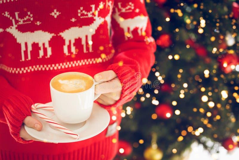 M?dchen, das eine Cappuccinoschale mit Zuckerstange h?lt Konzept des Weihnachtsfeiertags Festliches Feiertagsfeier bokeh lizenzfreies stockfoto