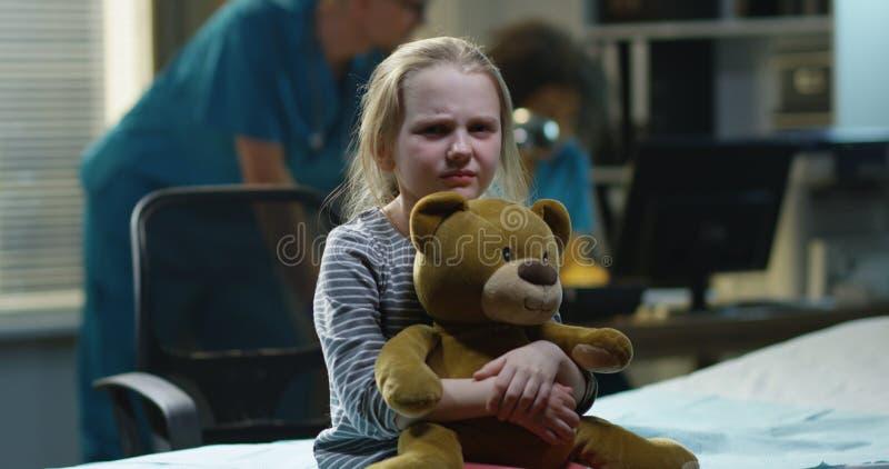 M?dchen, das im Krankenhaus mit Teddyb?ren sitzt lizenzfreies stockbild