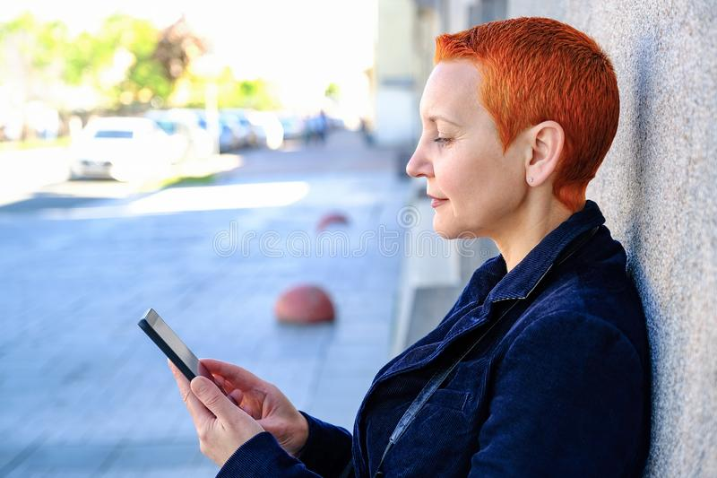 M?dchen, das SMS im Smartphone liest Das Gef?hl der frohen ?berraschung Der kurze Haarschnitt der Frauen Modernes stilvolles stockfotos