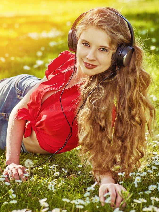 M?dchen in den Kopfh?rern fangen Rhythmusmusik auf gr?nem Gras stockbilder
