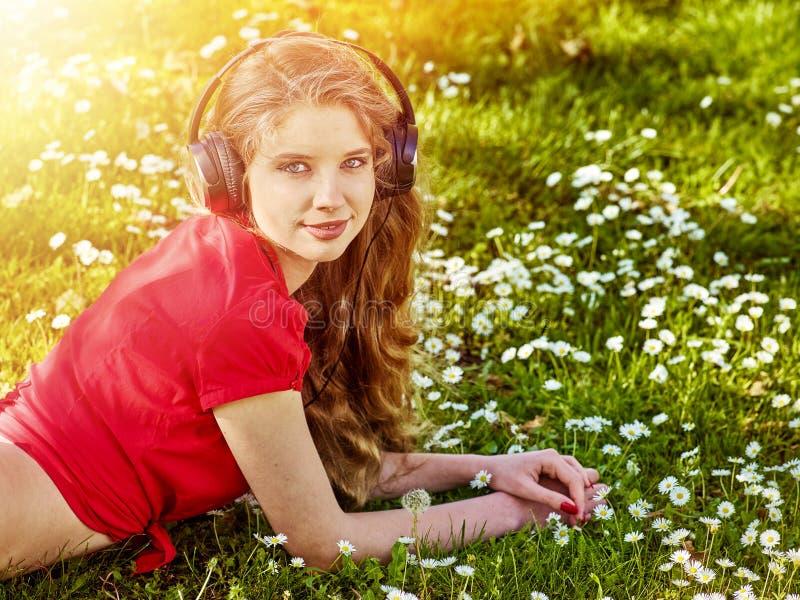 M?dchen in den Kopfh?rern fangen Rhythmusmusik auf gr?nem Gras lizenzfreie stockbilder