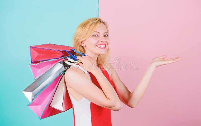 M?dchen genie?en zu kaufen oder erhielten gerade Geburtstagsgeschenke Griffb?ndel-Einkaufstaschen der Frau blauer rosa Hintergrun lizenzfreie stockbilder