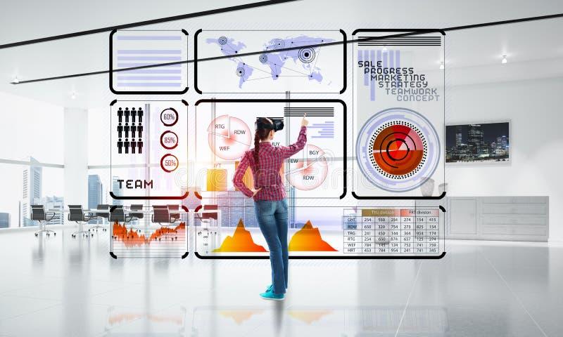M?dchen im B?roinnenraum in der Maske der virtuellen Realit?t unter Verwendung der innovativen Technologien Gemischte Medien lizenzfreie stockbilder