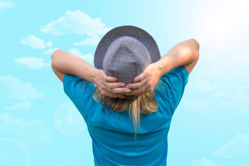 M?dchen im Hut Weiße mittlere Greisin bleibt zurück zu uns und setzt Hände hinter Kopf Hintere Ansicht ohne Gesicht lizenzfreies stockfoto