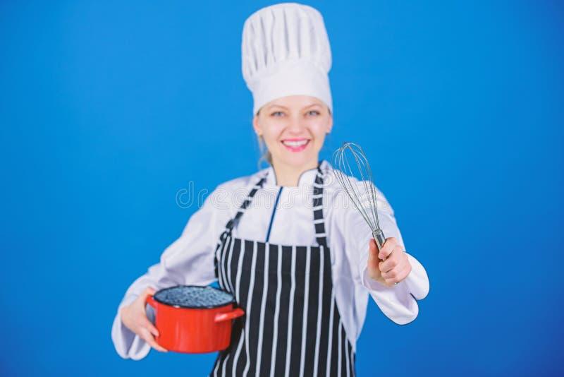 M?dchen im Schutzblech Eier oder Creme peitschend Fangen Sie, peitschende an oder schlagende Creme langsam zu wischen Gebrauchsha stockbild